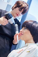 Hairdresser combing the hair of a woman. Hairdressing salon and Beauty Clinic.