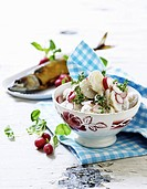 Potato salad with radishes served with smoked fish