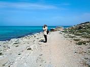 Photographer woman on Beach and view of beautiful sea, Cala Mesquida, Majorca island, Spain.