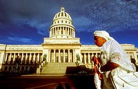 Woman santera passing the Capitolio Nacional, Havana, Cuba. Santería, also known as Regla de Ochá or La Regla de Lucumí is a syncretic religion of Car...