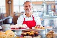 Barista smiling at camera behind counter