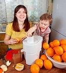 mother and daughter making orange juice
