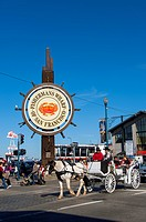 People riding in a horse carriage in front of the sign at the Fisherman's Wharf in San Francisco, California, USA.