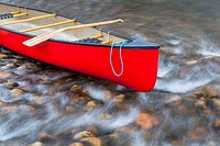 red canoe on a shallow river