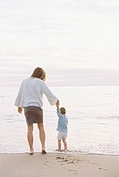 Woman standing on a sandy beach by the ocean, holding her young son's hand.