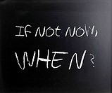 If not now, when? handwritten with white chalk on a blackboard.