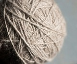 Close up of gray ball of yarn. Detail of equipment used for knitting and needlework as a hobby.