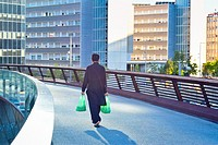 Back view of a man walking along a pedestrian bridge and holding two shopping bags. Crowded city buildings In the background. Barcelona, Catalonia, Sp...