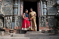 Two hindu women are standing at one of the entrance of the Channakeshava temple at Belur ( Karnataka, India).