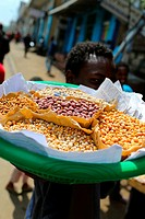 young Ehtiopian man selling nuts and corn on the street while carryiing his merchandises on the shoulder, Addis Ababa, Ethiopia, Africa.
