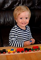 Little blond boy, 2 ½ years, play with a wood train.