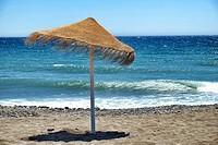Rustic brown sun umbrellas made of natural fibers on a nice beach in Costa del Sol, Andalusia, Spain