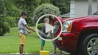 Single mother washing car at home with her two children in driveway with hose MR-11, MR-12, MR-13 Model Released