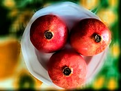 Three pomegranates in a white dish on a colourful table cloth, Ontario, Canada