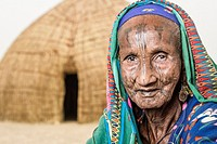 Portrait of an old Mbororo woman with typical scarifications on her face sitting down on the ground in front of her hut.