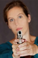 Caucasian woman defending herself using a handgun isolated on a gray background.