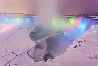 Horseshoe Falls illuminated at dusk with a frozen Niagara River. Niagara Falls, District Municipality of Niagara, Ontario, Canada.