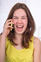 Teenage girl using a cellphone, and laughing