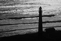 Lighthouse silhouette by ocean, Western Cape Province, South Africa.