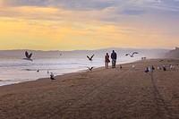 Couple walking along the beach,Monterey bay,California,USA.