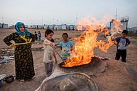 making a fire in the bread oven in Anwald refugee camp, Northern Iraq where 8000 Iraqi people have found refuge.