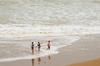 children playing in the water, Legzira Plage near Sidi Ifni, Morocco.