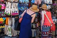 Two Young Women Shopping For Souvenirs, Corfu Old Town, Corfu, Greece.