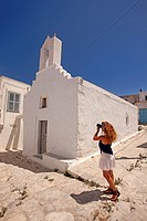 Woman taking photos in front of a whitewashed church in the old town Chora, Amorgos, Cyclades Islands, Greek Islands, Greece, Europe.