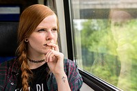 Tilburg, Netherlands. Young, red haired woman looking out the window of an intercity train while commuting home.