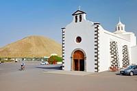 Church of Ermita de los Dolores in village of Mancha Blanca. Lanzarote, Canary Islands. Volcanic cone of Montana Tinache behind.