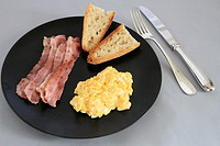 Breakfast with eggs, bacon and french bred.