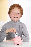 Little boy with red hair, happy putting a 20 euros banknote into the slot of his pink piggy bank