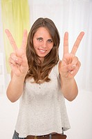 Young woman making the V of victory with her fingers to express her happiness and her success