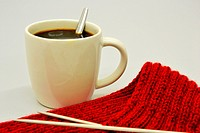 Cup of coffee next to knitting.
