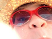 Closeup of a young girl wearing a straw hat and sunglasses.