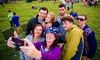 People taking a group selfie enjoying the The Big Tribute Music festival, Aberystwyth, August Bank Holiday weekend, Summer 2015.