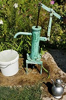 Hand pump with flowing water beside a garden in Shymkent South Kazakhstan Region.