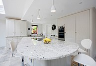 A modern white kitchen with granite worktops in the UK.