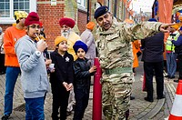 Children talk to a Sikh soldier of the British Army whilst waiting for the start of the Vaisakhi celebrations in Southampton (UK).