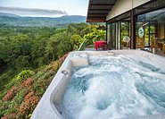 View from the hot tub of a small hillside vacation home, where the lush greenery of the jungle and the Turrialba volcano can be seen.