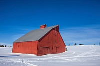 A red barn on the side of a small snowy hill in Moscow, Idaho.