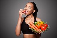 Beautiful healthy happy black asian woman eating delicious vegetables.