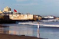 Female tourist shooting selfie, Atlantic ocean beach, Casablanca, Morocco.