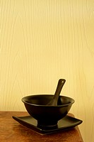 Dark bowl, plate and spoon sitting on corner of wooden table.
