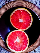 A three-circle design is formed by two halves of a grapefruit sitting in a brown bowl, Ontario, Canada