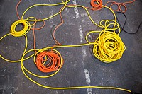 Electrical color cables lay in rolls over black ground.