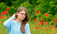 Beautiful young girl in the poppy field.