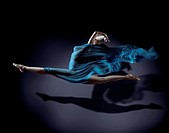 Beautiful young woman dancer in splits in mid-air with flowy blue cloth around her naked body and her shadow on dark background.