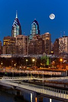 Philly Skyline Full Moon - A view to the Philadelphia Skyline during the blue hour at twilight. The illuminated urban skyline shows One and Two Libert...