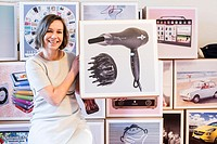 Zoetermeer, Netherlands. Portrait of an adult caucasian woman holding and showing a vintage hairdryer image.